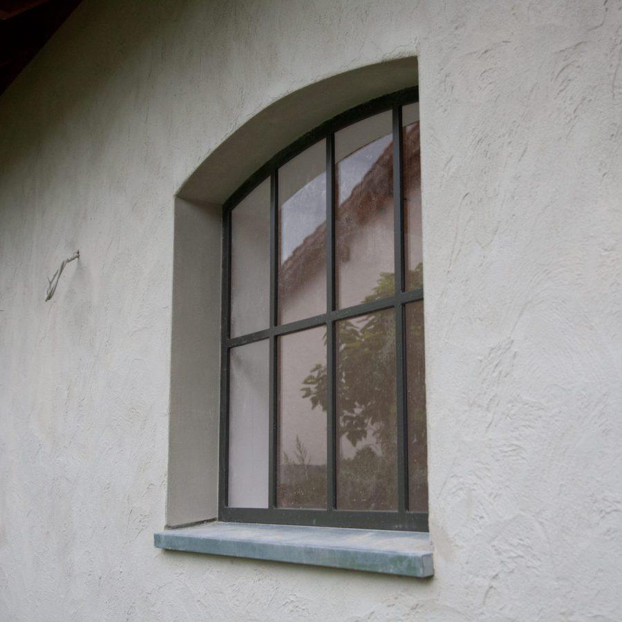 Details: Gitterfenster, Fensterblech aus Zink und ein strukturierter Kalkzementputz